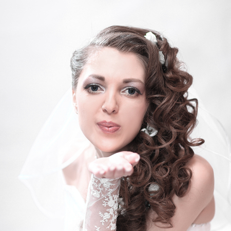 Young attractive bride in wedding dress sends a kiss