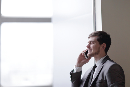 close up.businessman talking on smartphone while standing near an office window