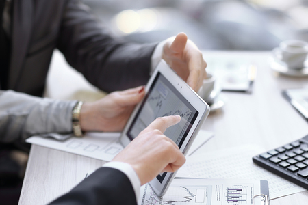 close up.Business adviser analyzing financial figures denoting the progress in the company