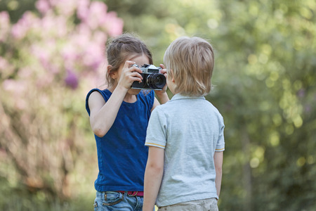 little girl takes a picture of her brother on a walk in the Park.