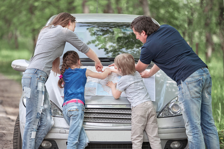 family with children standing near the faulty car .