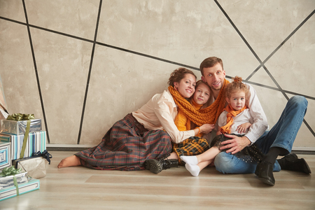 happy parents with their daughters sitting on the floor in a new apartment