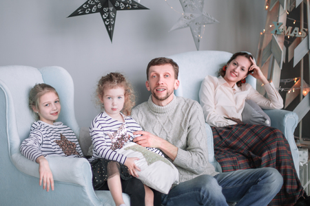 parents with their little daughters sitting in the living room Christmas evening.