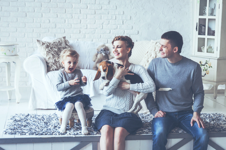 portrait of a happy family and their pet in a cozy living room