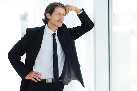 smiling businessman standing near window in office