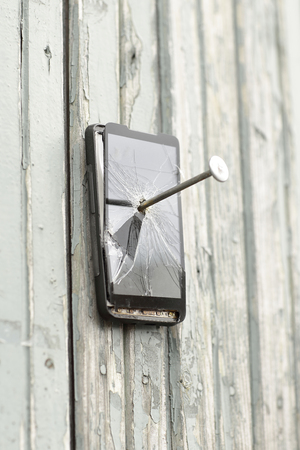 faulty mobile phone is nailed to an old fence