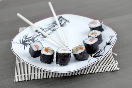 close-up of sushi and chopsticks on a white plate