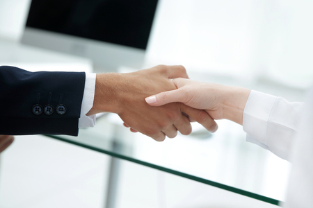 closeup .the financial partners shaking hands over a Desk . Reklamní fotografie