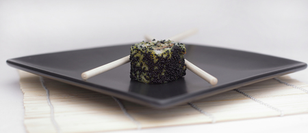 close-up of sushi and chopsticks on a black plate