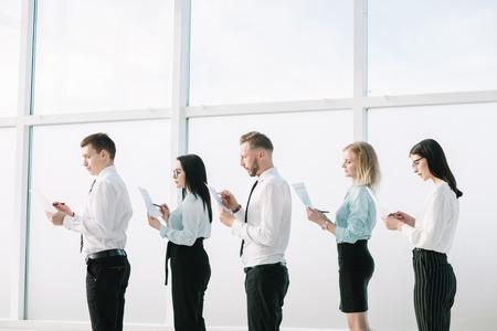 Nahansicht. Mitarbeiter mit Dokumenten, die in der Schlange stehen. Geschäftskonzept Standard-Bild
