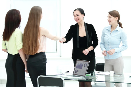 Satisfied older woman and young manager handshaking after signing contract in office