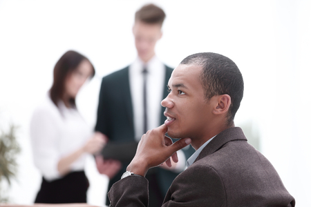 young successful businessman on background of office