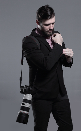 professional photographer with camera, adjusting a cufflink.isolated on grey background