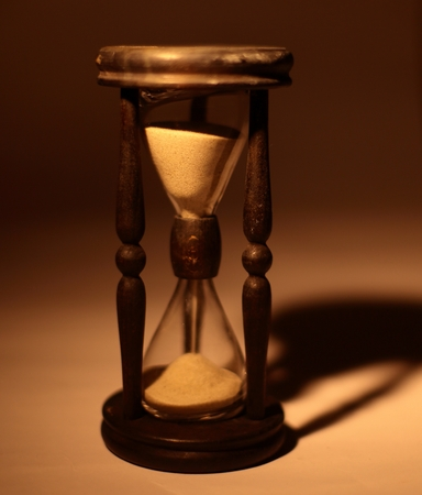 closeup of hourglass. isolated on blue background.