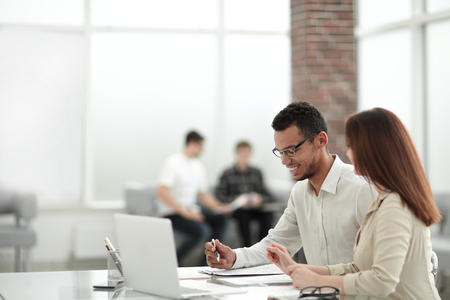 employees sitting at a table in the office .