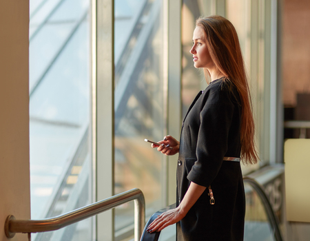 young business woman with mobile phone standing near office window.