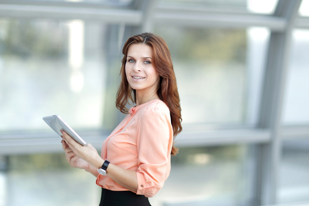 confident business woman with digital tablet on blurred office background. Stock Photo