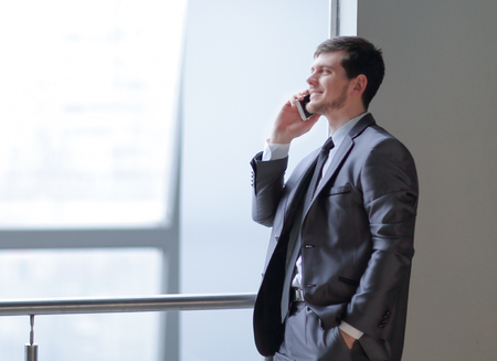 close up.businessman talking on smartphone while standing near an office window Stock Photo - 117804824