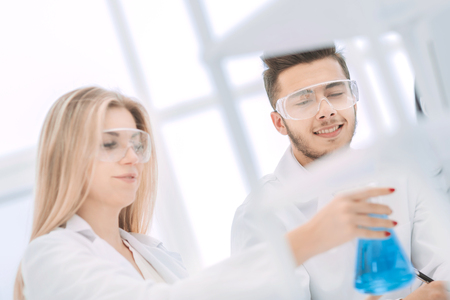 smiling scientist showing his colleague a flask of liquid.
