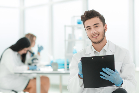 close up. a scientist doing writes the results of an experiment to a laboratory journal