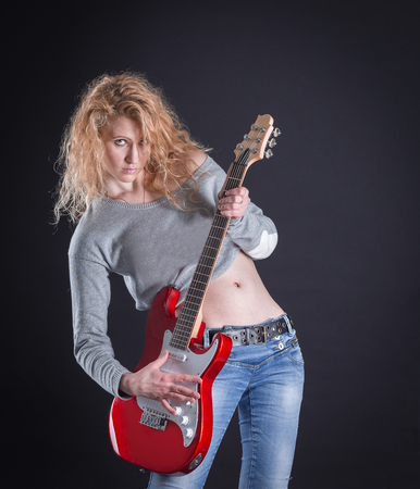 emotional rock singer with her guitar. isolated on a dark