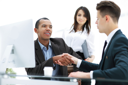 Handshake of business partners sitting at a table Desk