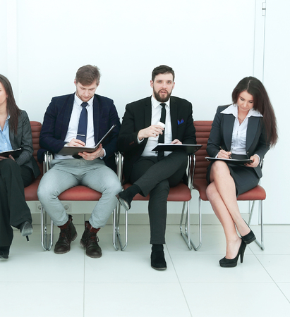 Business team with clipboards sitting in a row