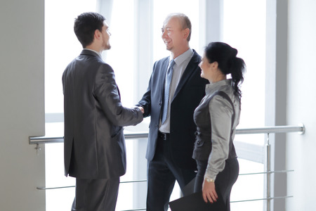 Smiling business team looking at a financial chart