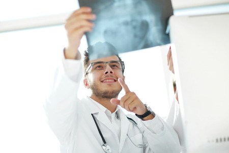 smiling orthopedist doctor looks at the x - ray of the patient Stock Photo