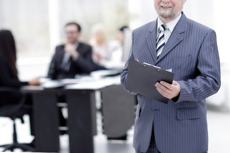senior businessman with clipboard standing in the office.