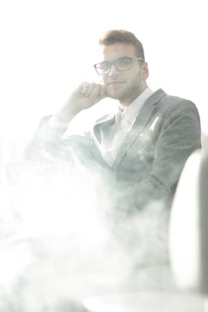 close up.pensive businessman with e-cigarette sitting in the break room