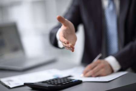 close up. businessman extending his hand to business partner Фото со стока