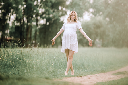 happy pregnant woman standing on a path in the Park