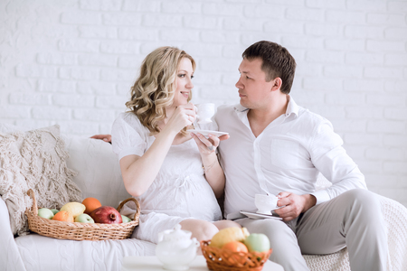 husband and his pregnant wife have Breakfast sitting on the couch 版權商用圖片