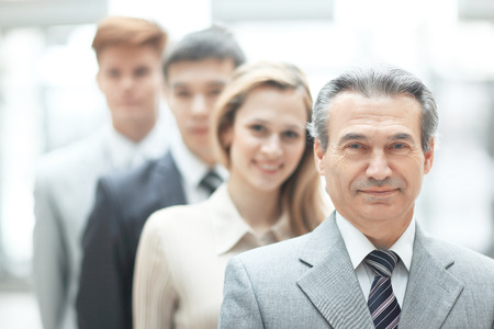 businessman standing in front of his business team on blurred office background