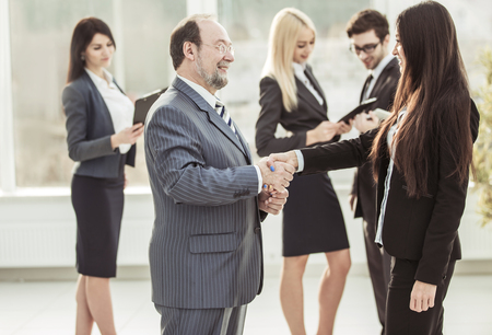 welcome handshake between lawyer and client on the background of business team