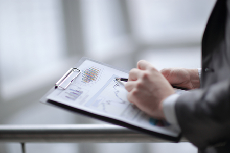 close up.businessman checking sales schedule.photo on blurred background