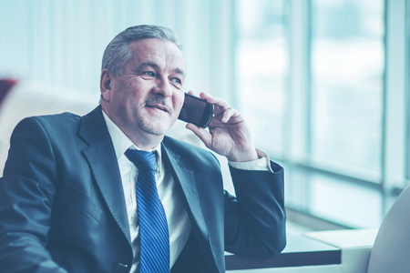 successful businessman talking on his smartphone sitting on couch in the office
