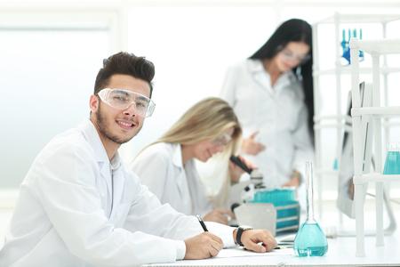 Nahaufnahme. Junger Wissenschaftler sitzt an seinem Schreibtisch im Labor