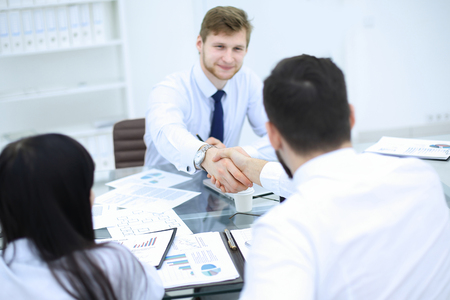 handshake of financial partners at a business meeting in the office