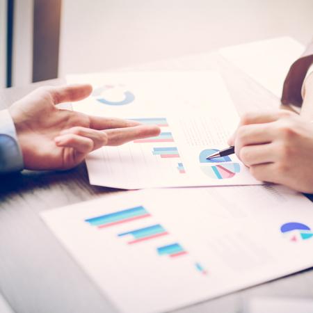 Image de mains humaines avec des stylos pointant sur un document commercial lors de la réunion