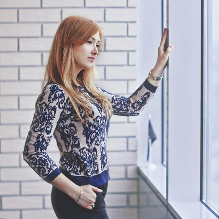 jeune femme regardant par la fenêtre du bureau.