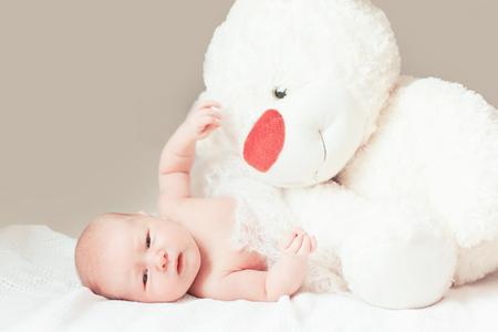 hübsches neugeborenes Mädchen mit einem großen Stofftier, das auf der Decke liegt.