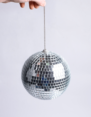 hand holding a mirror ball.isolated on gray background
