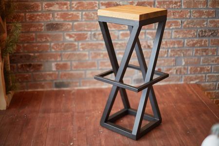 stylish bar stool on brick wall background. photo with copy space Foto de archivo