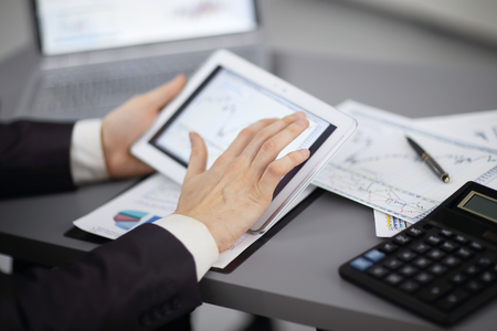 close up.the businessman uses a digital tablet to work with financial data.