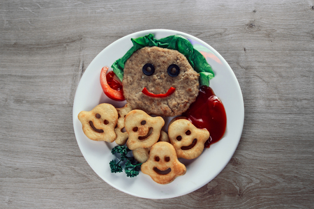 baby food. funny cutlet with vegetables and potato snacks on a white plate