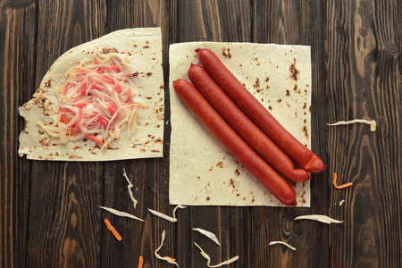 smoked sausage and cabbage on pita bread isolated on wooden background.