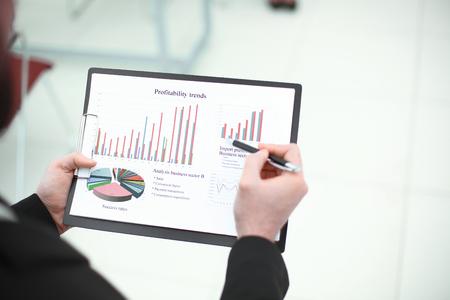 Rückansicht. Der Geschäftsmann überprüft den Finanzbericht. Foto mit Kopienraum.