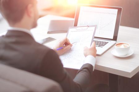 close-up.zakenman die financiële documenten controleert die aan de balie op kantoor zitten.